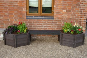 two recycled plastic wood garden planters beside a house wall & window