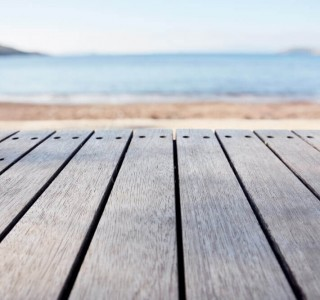 strip of decking overlooking a beach and blue skies