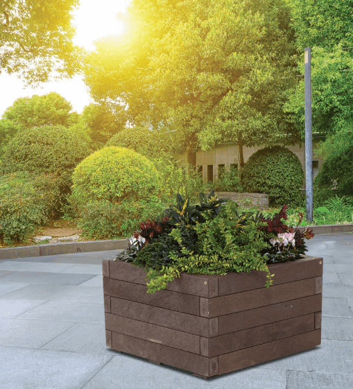 square recycled plastic wood planter on patio with plants and trees surrounding
