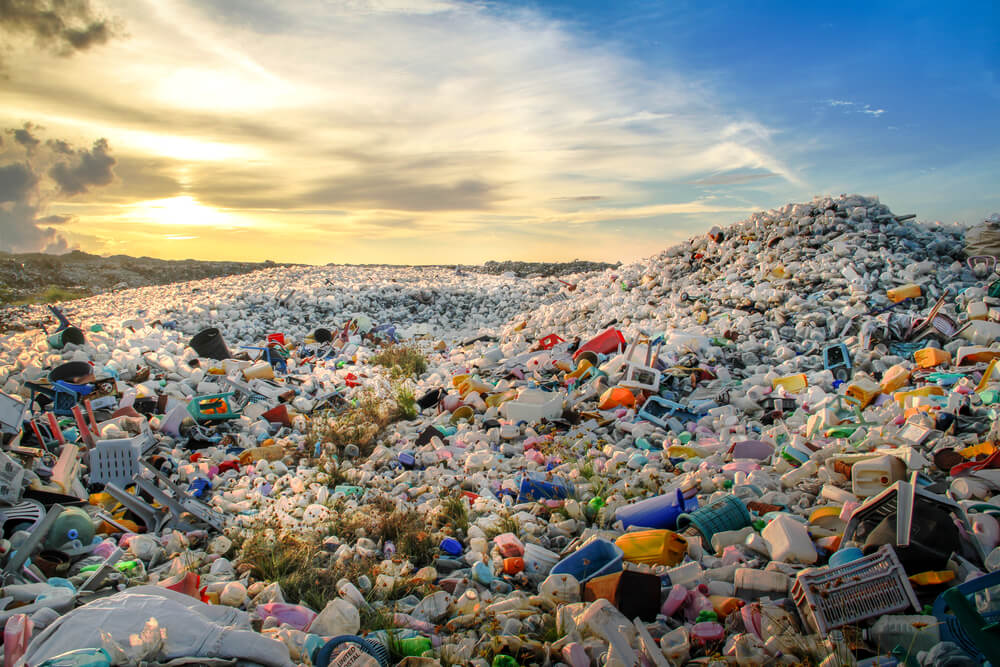 piled up waste at landfill site with sunset shining over