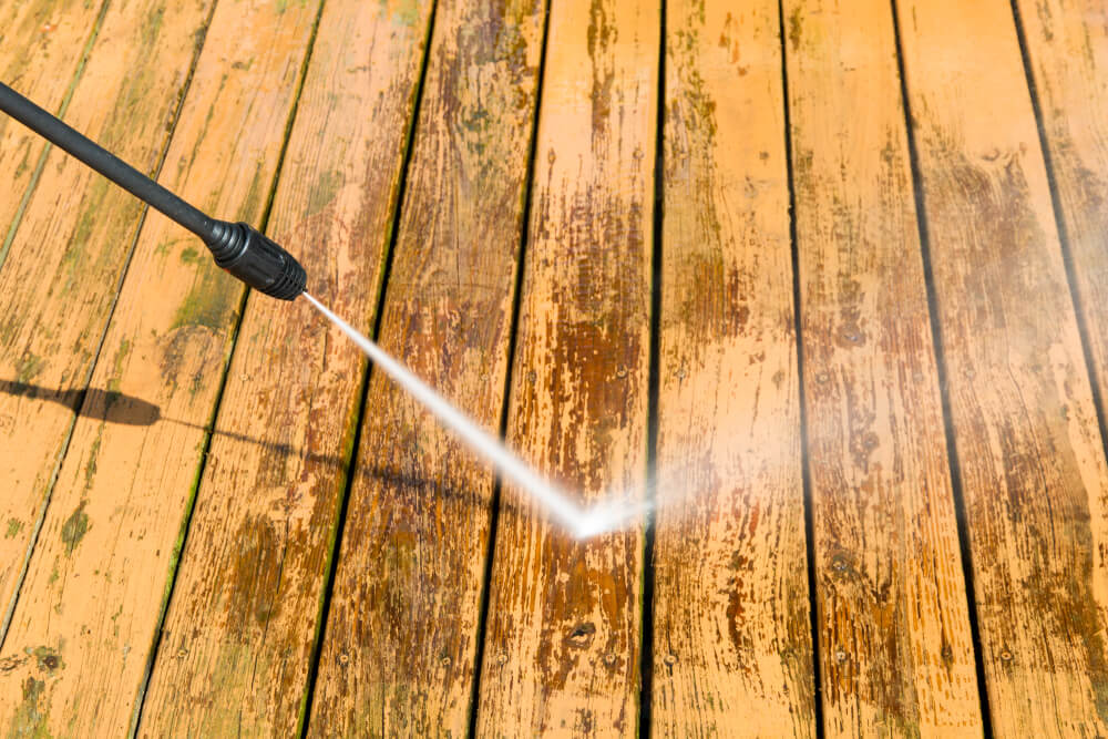 wooden decking being cleaned with pressure washer
