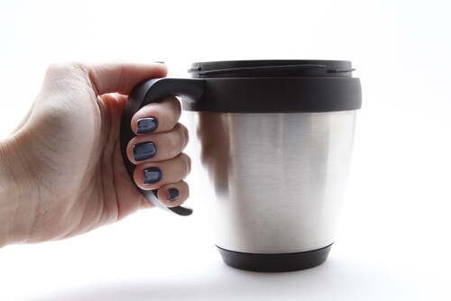person holding silver thermal coffee mug