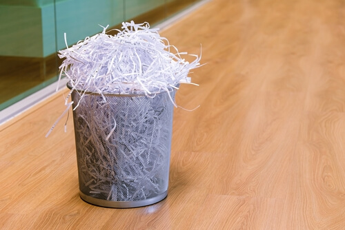 waste paper bin with shredded paper overflowing